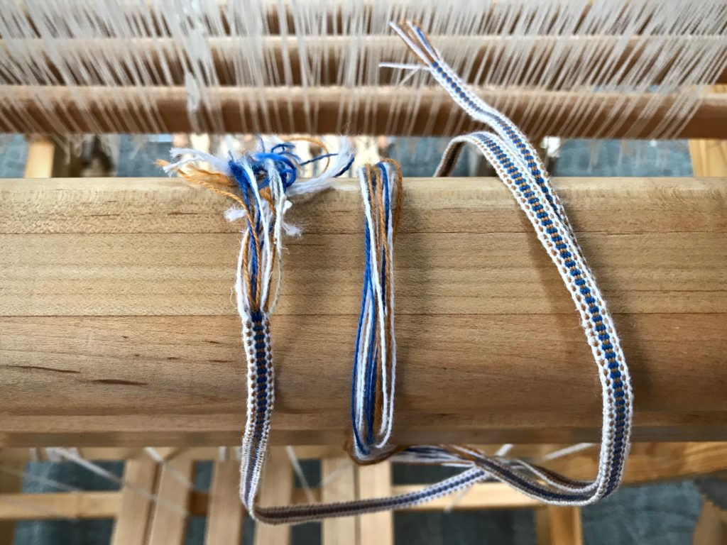 Woven band for hanging tabs on handwoven towels.