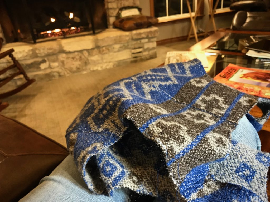Hand-stitching work by the fireplace.