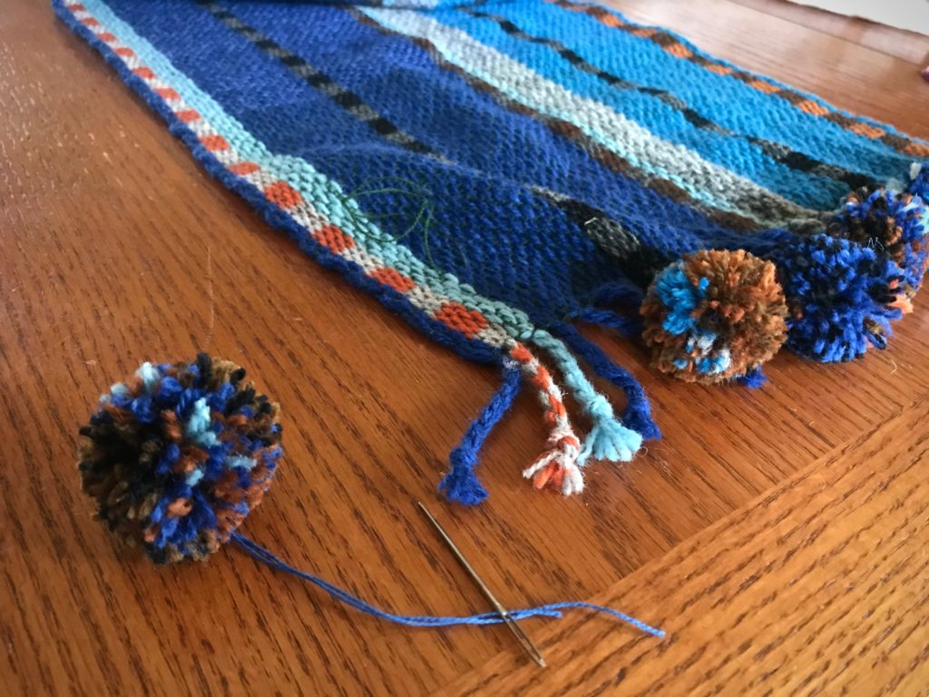 Adding pompom embellishments to the scarf.