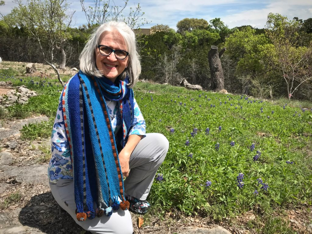 Winter scarf amid spring bluebonnets in Texas hill country.