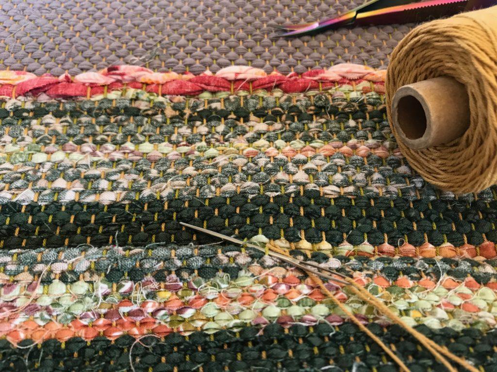 Hand hemming a rosepath rag rug.