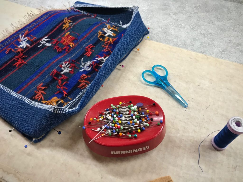 Constructing a small handwoven wool bag.