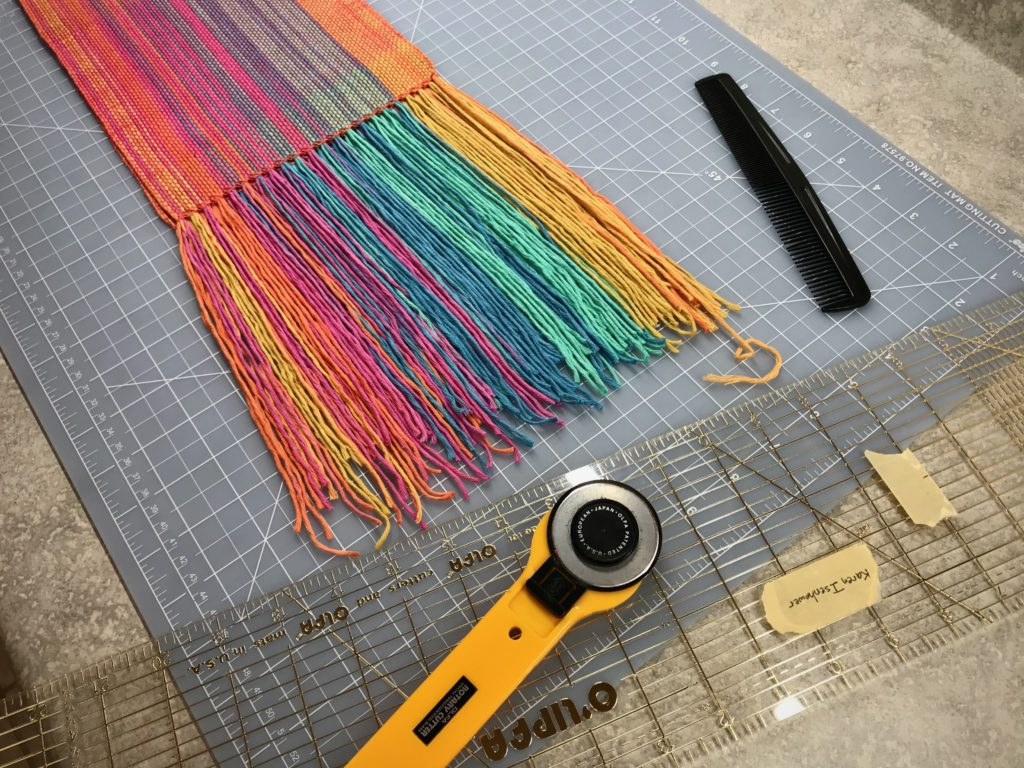 Trimming fringe on a handwoven scarf.