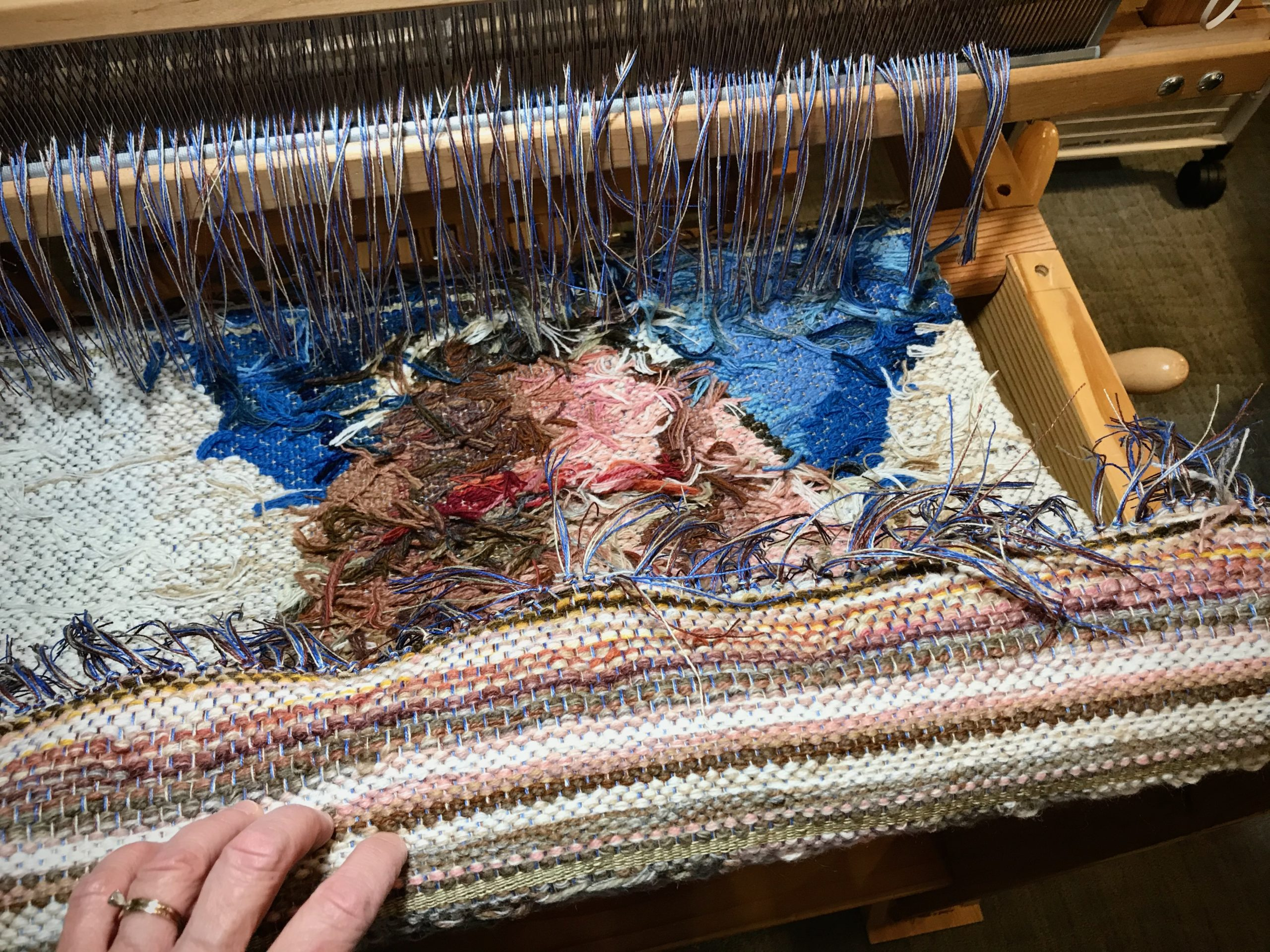 Cutting off a tapestry from the floor loom.