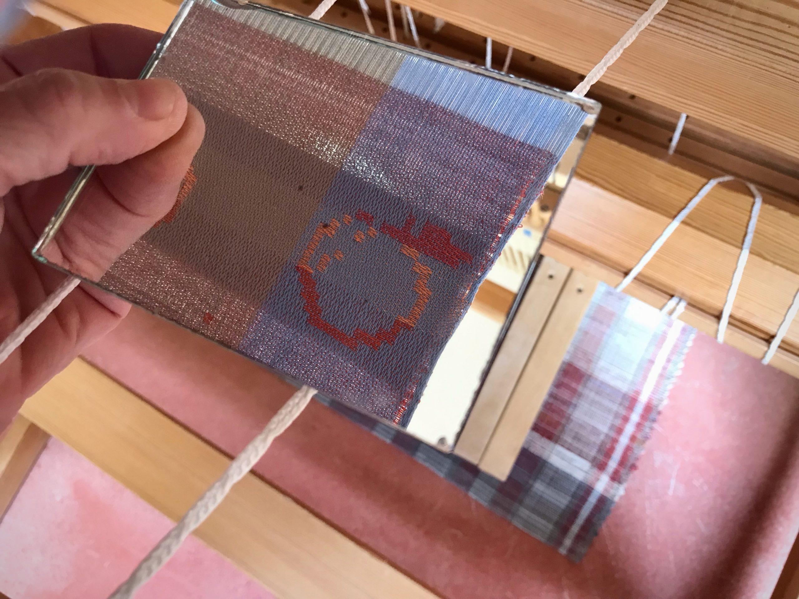 Mirror shows reversed side of drawloom fabric.